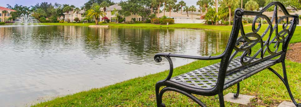 Park bench onlooking lake with fountain at Bellerive community | Vineyards Community Association - Naples, Florida